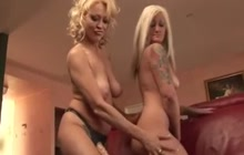Tattooed blonde takes strapon from behind